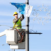 Don Knight | The Herald Bulletin<br /> John Binda hangs banners for the holiday season on the Eisenhower Bridge on Friday. The city will have a tree lighting and Christmas parade on December 2nd at 7p.m.
