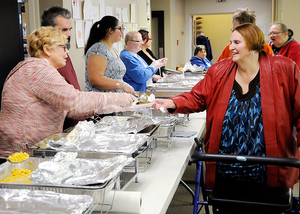Don Knight |  The Herald Bulletin<br /> Sharon Morgan gives Leigh Jennings a serving of stuffing during the Thanksgiving meal at South Meridian Church of God on Thursday. The church teamed up with the Christian Center who was offering meals in two locations.