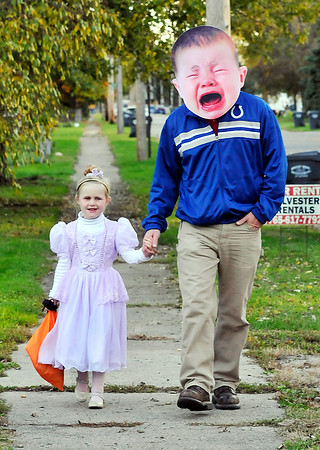 """John P. Cleary    The Herald Bulletin<br /> Princess Miriam Wlison, 5, trick-or treats along Crystal Street with her """"crybaby"""" father Avery Wilson Tuesday evening."""