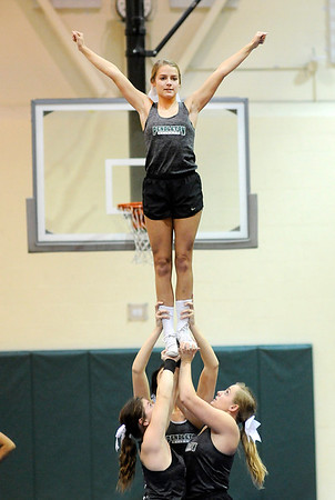 Don Knight |  The Herald Bulletin<br /> Rylee Tomey is lifted in the air by Katie Ferguson, Alexyss Jackson and Kylie Wolverton during Pendleton Heights cheerleading practice on Thursday.