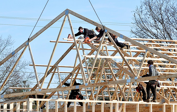 John P. Cleary |  The Herald Bulletin<br /> Workers from D.B. Builders of Hagerstown climb around the framework Monday as they install trusses for the new KT Pawn & Lown building being built at 38th and Main streets.