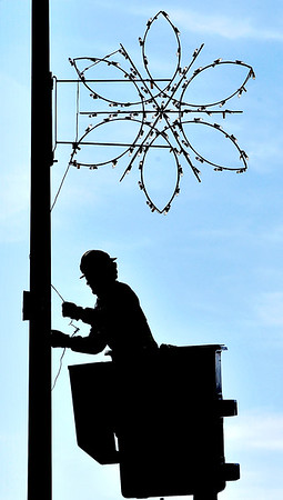 John P. Cleary    The Herald Bulletin<br /> Brenten Hiestand, from Anderson Light & Power, puts up holiday decorations on the light poles around the downtown area Tuesday morning as the holiday season is fast approaching.