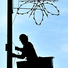 John P. Cleary |  The Herald Bulletin<br /> Brenten Hiestand, from Anderson Light & Power, puts up holiday decorations on the light poles around the downtown area Tuesday morning as the holiday season is fast approaching.