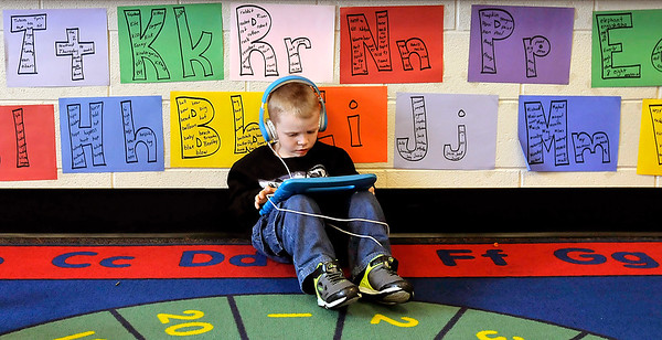 John P. Cleary |  The Herald Bulletin<br /> Killbuck School kindergarten student Devyn Reeves finds his own spot away from other students as he concentrates on using his tablet in April Dock's class.