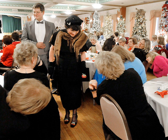 "John P. Cleary |  The Herald Bulletin<br /> Model Nancy Good shows off her shoes to a few of the ladies attending the Gruenewald Historic House ""Little Black Dress"" style show & luncheon Tuesday after she and her escort Bill Beeler walked the runway."
