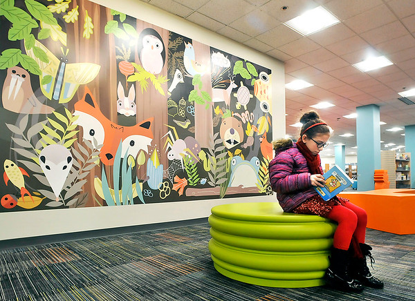 John P. Cleary |  The Herald Bulletin<br /> The newly remodeled Children's Department at Anderson Public Library features a large mural depicting different animals at the entrance of the second floor department. Here Adah Woodell, 10, looks over the book she checked out while waiting for family to finish up.
