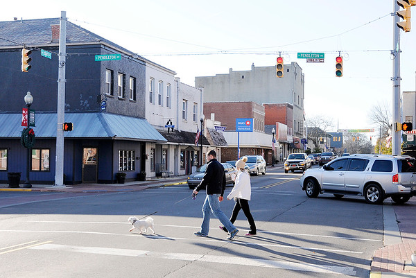 Don Knight |  The Herald Bulletin<br /> A pair of walkers cross State Street with their dog in Pendleton on Friday. The Pendleton Redevelopment Commission has proposed a Riverfront Development District for the town.