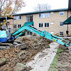 John P. Cleary |  The Herald Bulletin<br /> Wes Park, of A-1 Septic and Excavating, Franklin, Ind., digs out a trench for drainage pipe as work continues to rehab the Arbor Village Apartments on East Eighth Street this past week.