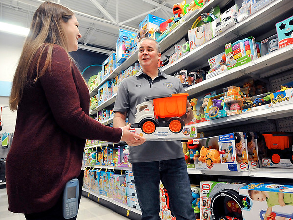 John P. Cleary |  The Herald Bulletin<br /> APD officer Mike Lee checks the toy inventory at Meijer with store manager Jennifer Petersen in preparation for this year's Cops and Kids program.