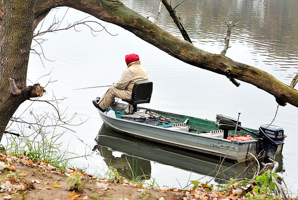John P. Cleary    The Herald Bulletin<br /> Framed by this tree this angler works the shoreline around Shadyside Lake on a cold, damp Monday afternoon.