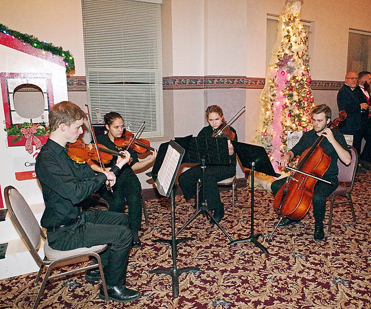 Mark Maynard | for The Herald Bulletin<br /> A string quartet from Anderson University composed of Luke Gray, Grace Roth, Hannah Gross, and Rob Lowman was on hand at the Paramount Theatre on Saturday evening to entertain those attending the Festival of the Trees Gala.