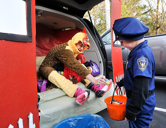 "John P. Cleary |  The Herald Bulletin<br /> Gavynn Spaeth, 14, gives Zander McCormick, 6, a candy-filled egg from his ""hen house"" during Trunk or Treat at the Anderson Moose Lodge 150 Tuesday evening."