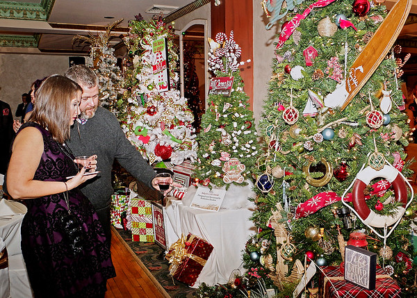 "Mark Maynard | for The Herald Bulletin<br /> Samantha and Nic Smock of Noblesville consider bidding on a tree decorated to prove that ""Life is Better on the Lake"" at Saturday's Festival of the Trees Gala."