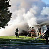 John P. Cleary |  The Herald Bulletin<br /> heavy smoke fills the sky as firefighters from multiple departments battle a house fire on Indiana 9 and County Road 375N Wednesday morning.