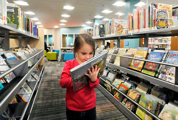 John P. Cleary |  The Herald Bulletin<br /> Mila Anne Brandl, 4, picks out a book from the new shelving in the newly remodeled Children's Department at Anderson Public Library this past week. As part of the remodeling these new shelves puts the book covers down on the children's level to better see them and make a selection.