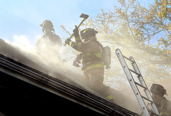 John P. Cleary    The Herald Bulletin<br /> Anderson firefighters battle a house fire, here venting the roof, at 2219 Central Avenue Thursday afternoon.