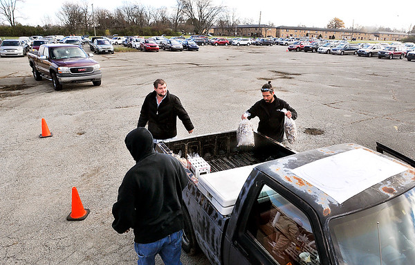 John P. Cleary |  The Herald Bulletin<br /> Tailgate food distribution by Second Harvest Food Bank at the former Kmart parking lot on Nichol Avenue.  Volunteers load food in the bed of this truck as all the vehicles in the background wait their turn in line.