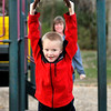 John P. Cleary |  The Herald Bulletin<br /> Acelin Abshire, 6, enjoys the warm November day playing at the Shadyside Park playground on Alexandria Pike Monday afternoon with family. Here Acelin swings his body to slide along the bar as grandmother, Misty Laymon, background, watches after she helped him get started with push.