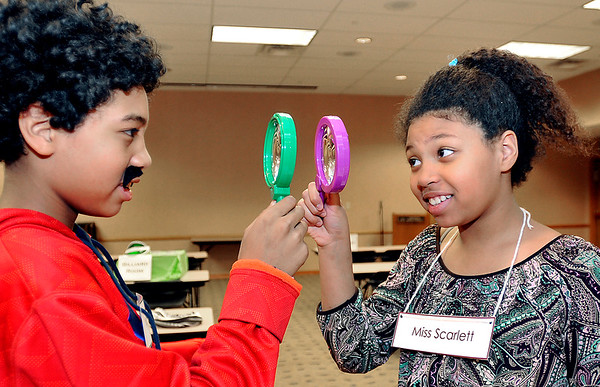 John P. Cleary   The Herald Bulletin<br /> Kailani McCloud, 13, aka Mr. Green, and Nani McCloud, 11, aka Miss Scarlett, prepare to test their detective skills as they play Life Size Clue at the Anderson Public Library Monday evening.