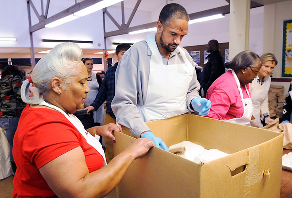 Don Knight   The Herald Bulletin<br /> Daniel Baxter fills a box with a delivery order during the Gospel Highlight Radio Broadcast Community Thanksgiving Day Dinner at the Geater Center on Thursday.