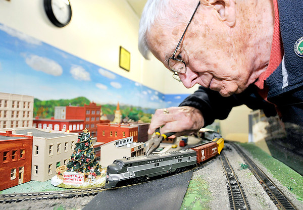 John P. Cleary | The Herald Bulletin   THB file photo<br /> Madison County Historical Society volunteer Curt McGuire touches up some scenery as a train on the N gauge model railroad layout passes under him as he works at the History Center.