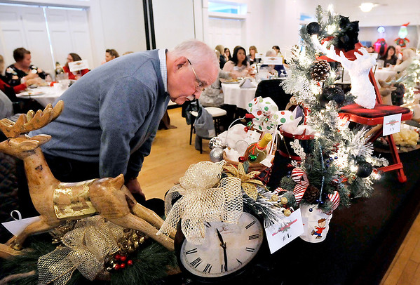 John P. Cleary | The Herald Bulletin<br /> Don Apple takes a close look at some of the items up for bid during the Anderson Noon Exchange Club's Christmas Auction and Holiday Bazaar Tuesday at Edgewood Golf Course & Event Center.