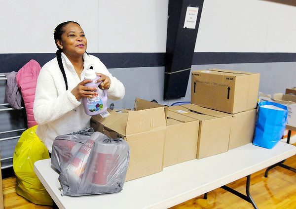 Don Knight   The Herald Bulletin<br /> Phoebe Jones hands out houshold items during the Gospel Highlight Radio Broadcast Community Thanksgiving Day Dinner at the Geater Center on Thursday.