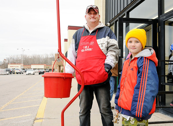 Don Knight | The Herald Bulletin<br /> Kim Conley and his nephew Devin Auler, 10,  ring the bell at the Salvation Army's Red Kettle outside of Roses on Thursday. Each Christmas season the Salvation Army helps provide about 1,500 children with toys, food and clothes.