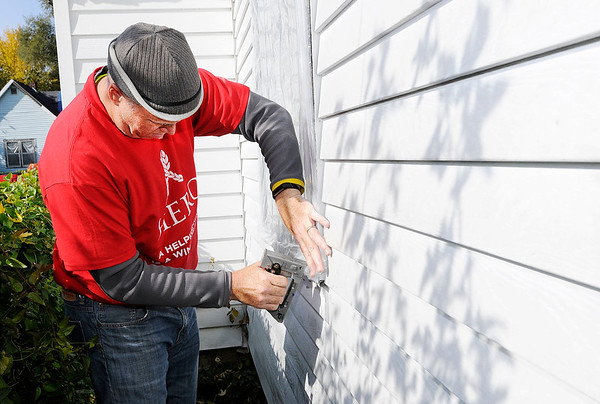 Don Knight | The Herald Bulletin<br /> Mark Thacker staples plastic around a window during United Way's Operation Weatherization on Saturady. Thacker was part of the team Harrah's Heros representing Harrah's Hoosier Park. The annual program helps home owners prepare for the coming winter months.