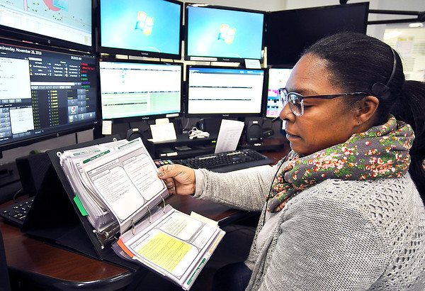 John P. Cleary   The Herald Bulletin<br /> Madison County Dispatch Center dispatcher Sulyn Wilkerson goes through her flip file of medical guidecards each dispatcher has to go to on a medical emergency call to help provide aid to the caller until first responders arrive at the scene. With the new Power Phone system the emergency medical treatment information will instantly appear on the dispatchers computer screen to relay to the 911 caller.<br /> <br />  going to new telephone service that will automatically provide medical advice.