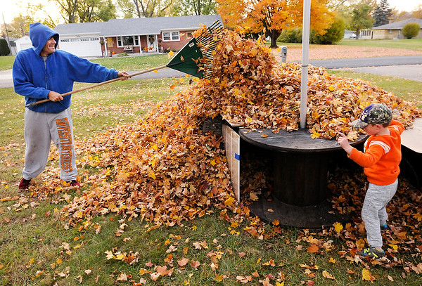 Don Knight | The Herald Bulletin<br /> James Kerr and his son Gavin, 3, build a fort while raking leaves in their front yard on Thursday.