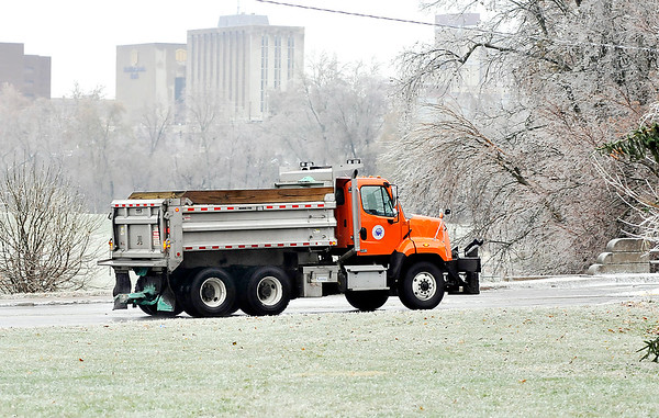 John P. Cleary   The Herald Bulletin<br /> With a layer of ice covering everything this Anderson Street Department truck spreads salt along Main Street at the Truman Bridge Thursday morning after an ice storm hit the area overnight.