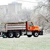 John P. Cleary | The Herald Bulletin<br /> With a layer of ice covering everything this Anderson Street Department truck spreads salt along Main Street at the Truman Bridge Thursday morning after an ice storm hit the area overnight.