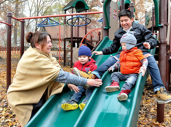 John P. Cleary   The Herald Bulletin<br /> Ronda Rhea helps her grandchildren, Conner and Cylas, come down the slide as her son Jordan Vasquez slides down behind them as they play at Shadyside Park last week.