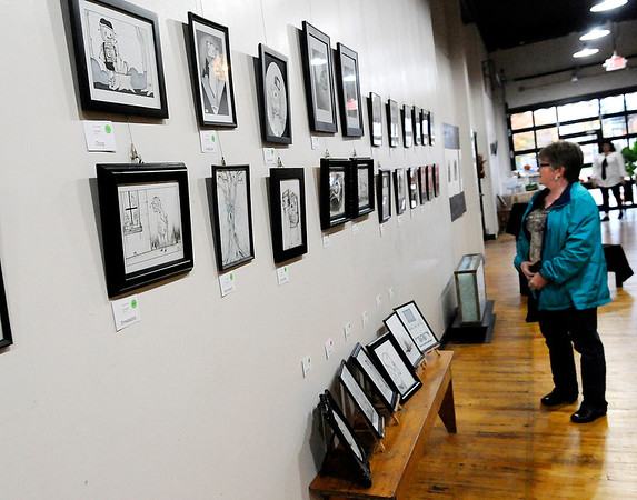 Don Knight | The Herald Bulletin<br /> Tina Lewis looks at artwork by Caryn Gorman at the A Town Center during the First Friday Art Walk on Friday. Several local artists and businesses participate in the walks that take place on the first Friday of each month.