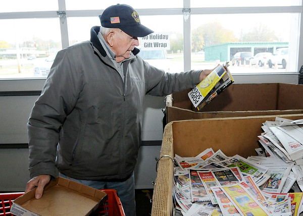Don Knight | The Herald Bulletin<br /> Robert E. Moore recycles magazines at the Madison County Recycling Center on Thursday.