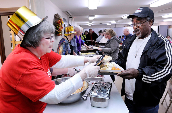 Don Knight   The Herald Bulletin<br /> Cecelia Lester gives Lawrende Robinson a roll during the annual Lawson/Wellman meal at Cross Roads United Methodist Church on Tuesday. The meal is held on Tuesday instead of Thursday so people can ride a CATS bus to the church which the city offers for free.