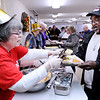 Don Knight | The Herald Bulletin<br /> Cecelia Lester gives Lawrende Robinson a roll during the annual Lawson/Wellman meal at Cross Roads United Methodist Church on Tuesday. The meal is held on Tuesday instead of Thursday so people can ride a CATS bus to the church which the city offers for free.