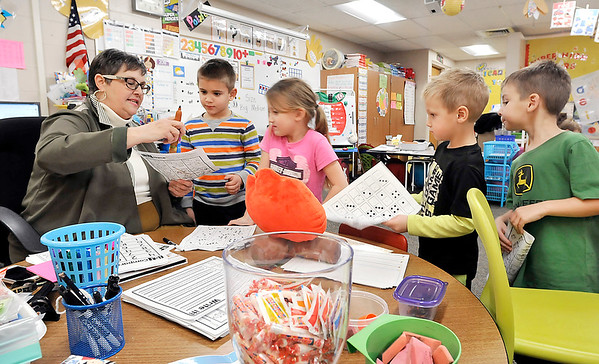 John P. Cleary   The Herald Bulletin<br /> Lapel Elementary School Kindergarten teacher Kathryn Parker checks a students paper as others wait in line for their turn.