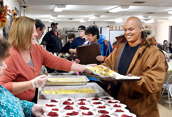 Tony White, right, is all smiles as Pam Griffis serves him his plate of food Tuesday during the annual John Lawson/Fran Wellman Memorial Thanksgiving Dinner at Cross Roads United Methodist Church. This is the 14th year the congregation has offered the free holiday feast at their 2000 N. Scatterfield Road location.