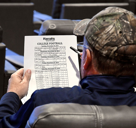 These patron studies the college football odd sheet while at The Book sports betting facility at Hoosier Park Racing & Casino.