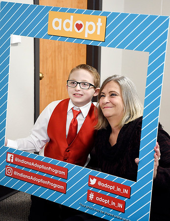 Xzavier Swindell, 8, gets his framed photograph taken with his grandmother Patricia Swindell as she adopted him Thursday during National Adoption Day in Madison County Circuit Court I.
