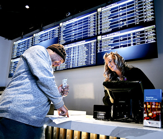 With cash in hand Ronald Johnson, of McCordsville, checks his odds sheet as he places his bets on this weeks NFL games with Jessica McColley, sports book writer at The Book sports betting facility at Hoosier Park Racing & Casino.