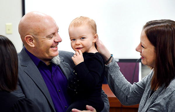 Zachary Sparks is all smiles as he holds his newly adopted daughter Abigail, 1, with her mother Janelle Sparks at the end of their adoption proceeding with Judge Angela Sims in Madison County Circuit Court I as part of National Adoption Day Thursday in Madison County.