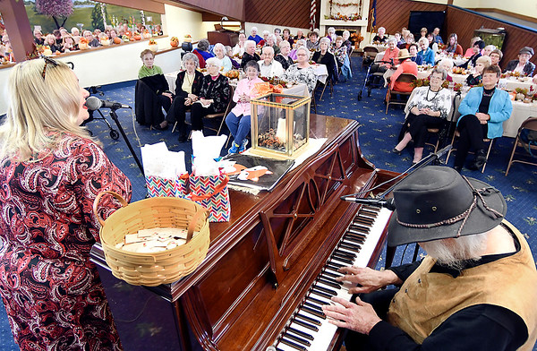 Martha Green and Dan Daugherty entertain the crowd gathered for the Isabel Society's Fall Harvest luncheon Wednesday held at the Harter House.