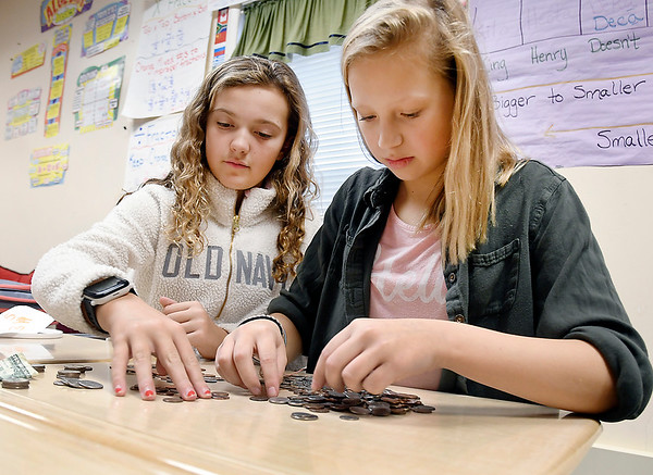 Sixth-grade students, Brynley Dowden and Addie Bates of Shannon Howell's Alexandria Intermediate School class, counts money that is being collected by the student body for the Make a Wish Foundation.