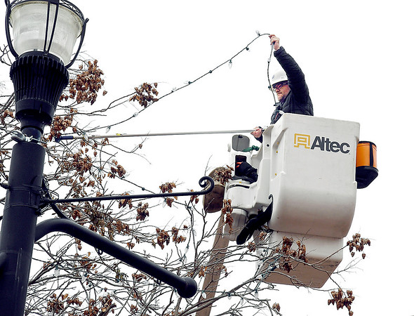 Anderson City Water Department employee Josh Castor uses a long pole to extend his reach as he strings holiday lights on one of the trees in Dickmann Town Center Thursday. Workers have been busy this week decorating the park in preparation for the holidays.