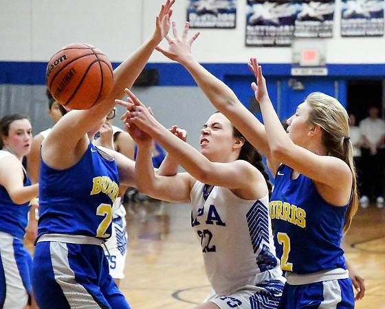 Chelsea Klepfer, of APA, center, tries to split Burris defenders Hannah Kreider and Hannah Houser but looses control of the ball.
