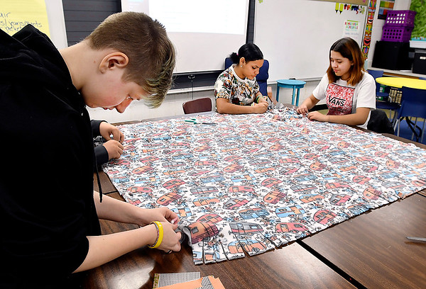 COMPASS students were making blankets Tuesday as part of the school's third annual Day of Gratitude. Here Max Krieg, 7th grade, ties strips on one end as Deaira Jackson, 7th grade, and Melissa Bernal-Garcia, 9th grade work the other end of the blanket they are helping make.