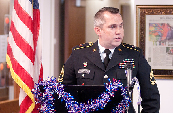 Sgt. 1st Class James Reynolds speaks during a tribute to veterans at Harter House on Friday.